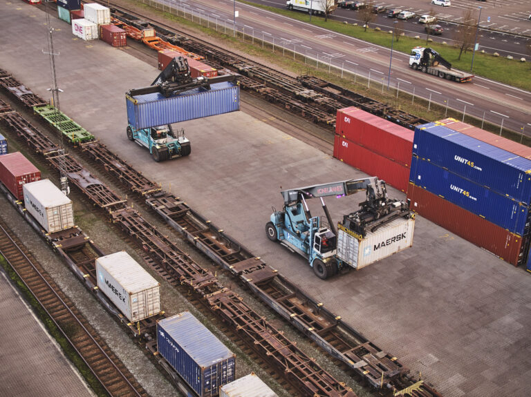 Combiterminal med järnvägsspår. Två truckar som förlyttar containrar. Väg och trafik i bakgrunden.