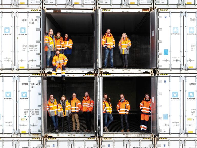 Hamnpersonal som står inuti i öppna containrar